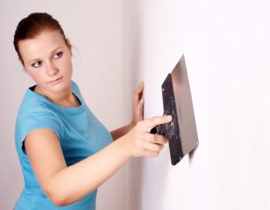 девушка выравнивает стену